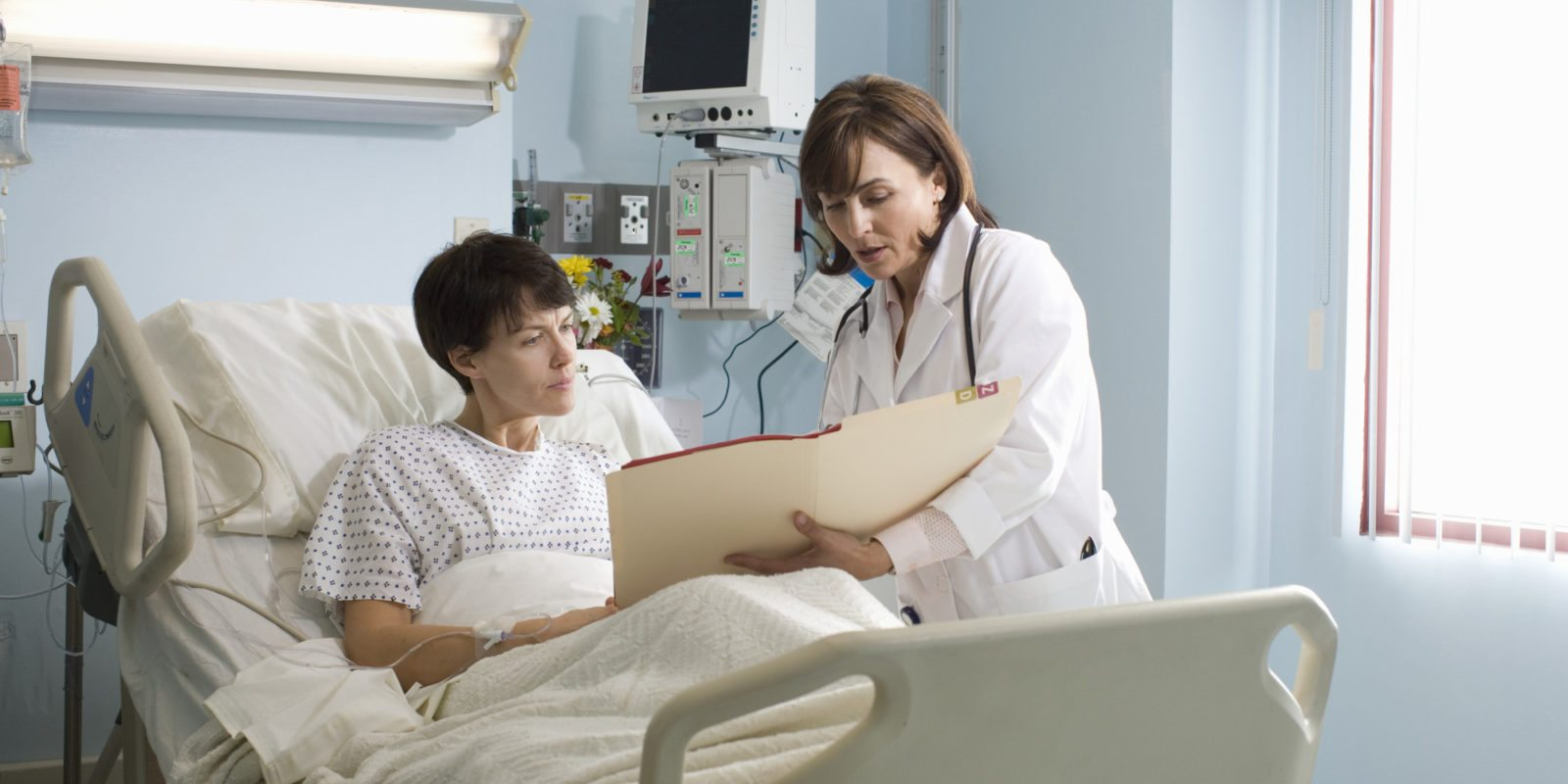 Female doctor showing medical chart to female patient lying in hospital bed